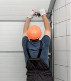 Man installing an overhead door